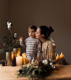 Glückliche mutter und ihr kind mit weihnachtsdekoration. hygge gemütliches zuhause. glückliche mutterschaftszeit
