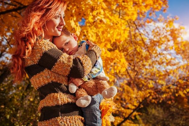 Glückliche mutter und ihr kleiner sohn, die in herbstwald geht frau, die ihr kind hält