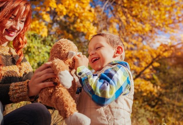 Glückliche mutter und ihr kleiner sohn, die spaß im herbstwald hat kind spielt mit einem spielzeug
