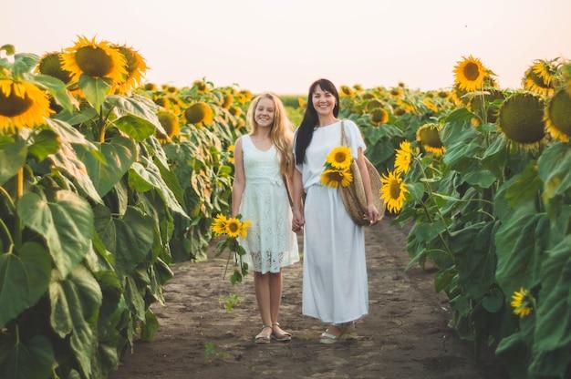 Glückliche mutter und ihre jugendliche tochter im sonnenblumenfeld. im freien lebensstil glück
