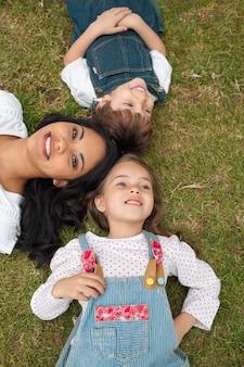 Glückliche mutter und ihre kinder, die auf dem gras liegen