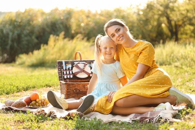 Glückliche mutter und ihre kleine tochter beim picknick im park