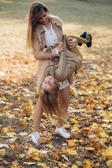 Glückliche mutter und ihre schöne tochter haben spaß und gehen im herbstpark spazieren.