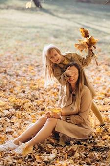 Glückliche mutter und ihre schöne tochter sitzen und haben spaß zwischen den gelben blättern im herbstpark.