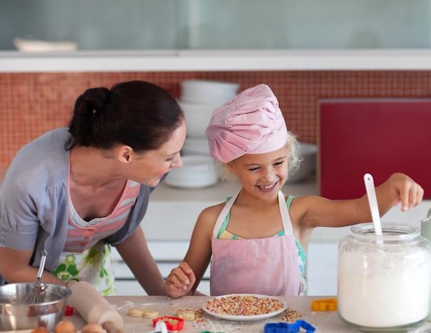 Glückliche mutter und ihre tochter, die in einer küche backt