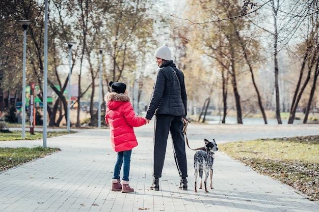 Glückliche mutter und ihre tochter gehen mit hund im herbstpark