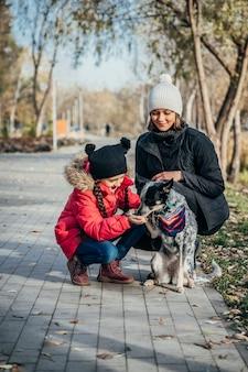 Glückliche mutter und ihre tochter spielen mit hund im herbstpark