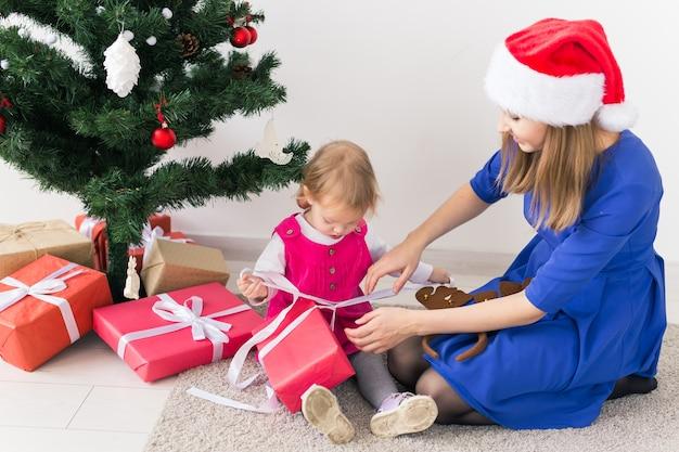 Glückliche mutter und junges mädchen, die weihnachtsgeschenke öffnen