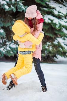 Glückliche mutter und kind genießen schneebedeckten tag des winters