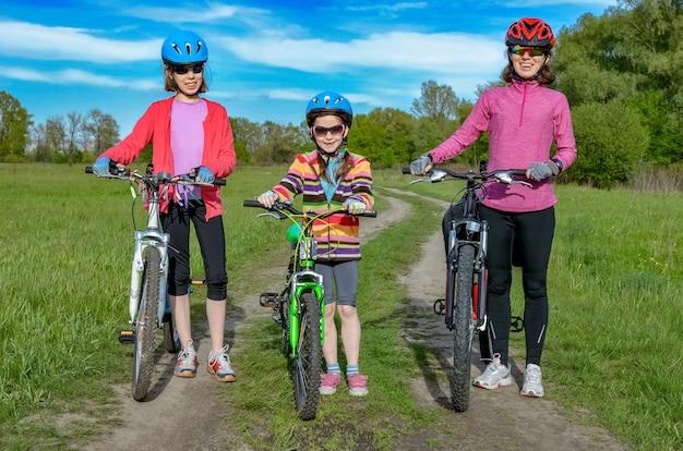 Glückliche mutter und kinder auf fahrrädern radfahren im freien im park aktiver familiensport