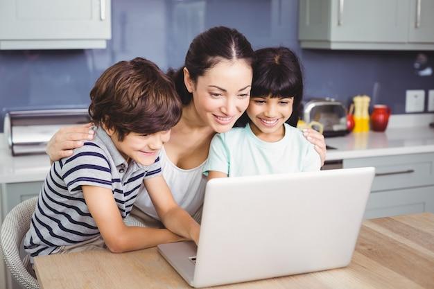 Glückliche mutter und kinder, die an laptop arbeiten