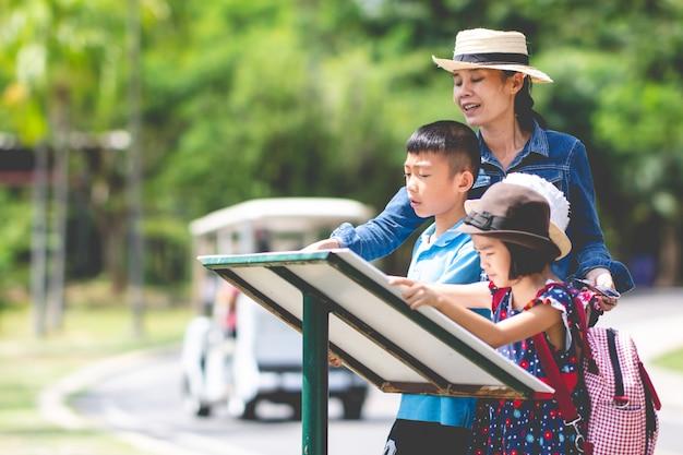 Glückliche mutter- und kinderfamilie reisen in safari auf sommer