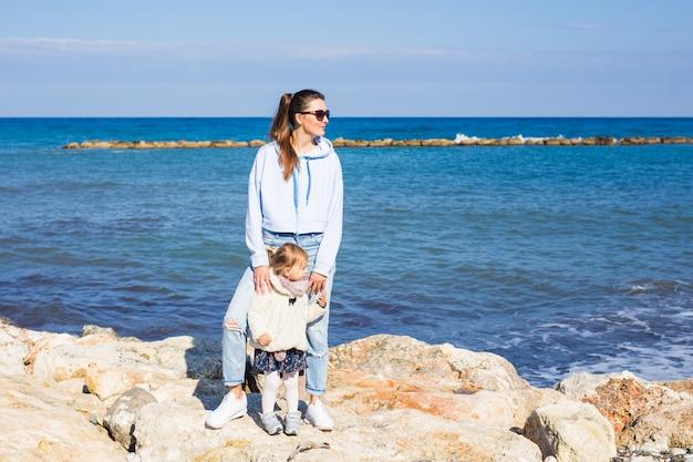 Glückliche mutter und kleine tochter am strand