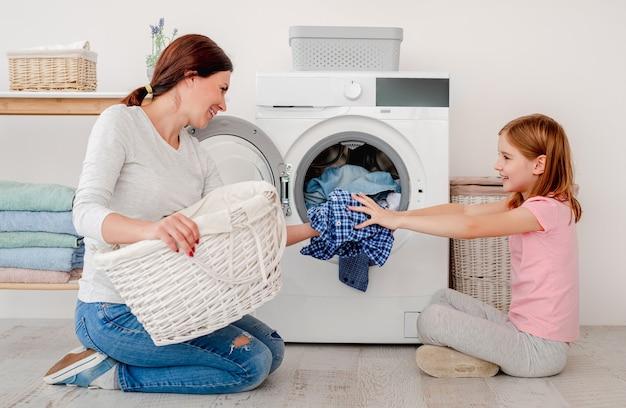 Glückliche mutter und kleine tochter, die wäsche mit maschine im hellen raum waschen