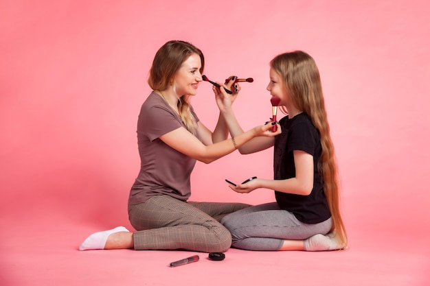 Glückliche mutter und kleine tochter in freizeitkleidung sitzen, bürsten halten und make-up füreinander auf rosa hintergrund machen. konzept, zeit zusammen mit kindern und familienbeziehungen zu verbringen