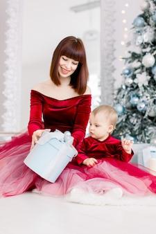 Glückliche mutter und kleine tochter in roten kleidern, sitzend nahe weihnachtsbaum, und eröffnungsgeschenk
