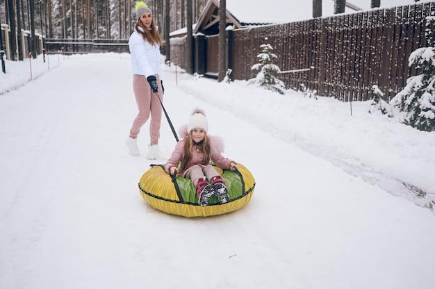 Glückliche mutter und kleines süßes mädchen in rosa warmer oberbekleidung, die spaß haben reitet aufblasbare schneeröhre im schneeweißen kalten winterwald draußen