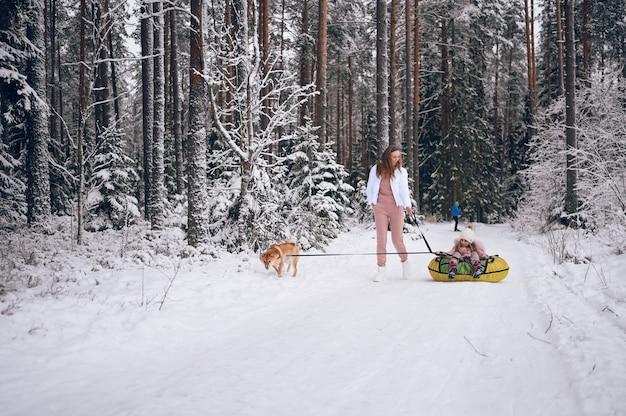 Glückliche mutter und kleines süßes mädchen in rosa warmer oberbekleidung, die spaß hat, reitet aufblasbare schneeröhre mit rotem shiba inu-hund im schneeweißen kalten winterwald im freien