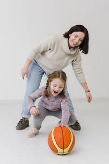 Glückliche mutter und mädchen, die basketball spielen