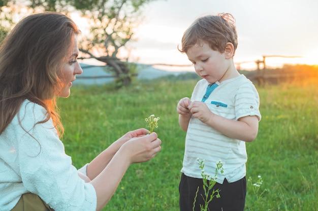 Glückliche mutter und sohn auf natur auf sonnenuntergang