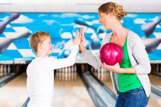 Glückliche mutter und sohn, die zusammen im bowlingzentrum spielen