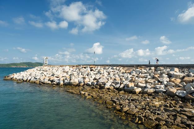 Glückliche mutter und sohn rennen zum leuchtturm und dock von khao laem ya