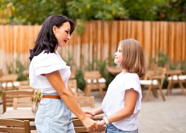 Glückliche mutter und teenager-tochter, die draußen auf der café-terrasse stehen und sich gegenseitig die hände halten. familienkonzept