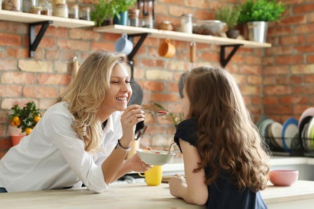 Glückliche mutter und tochter beim frühstück in der küche