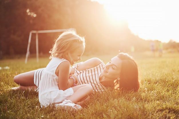 Glückliche mutter und tochter, die in einem park in der sonne an einem hellen sommer der kräuter umarmen.