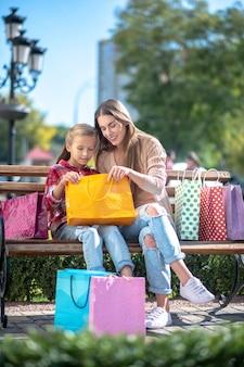 Glückliche mutter und tochter, die in einkaufstasche auf parkbank schauen