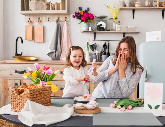 Glückliche mutter und tochter, die kleinen kuchen macht