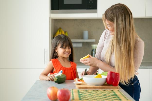 Glückliche mutter und tochter, die salat mit zitronendressing kochen. mädchen und ihre mutter schälen und schneiden gemüse auf küchentheke, plaudern und haben spaß. familienkoch- oder gesunde ernährungskonzept