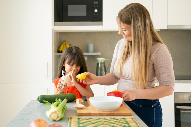 Glückliche mutter und tochter, die spaß beim gemeinsamen abendessen haben. mädchen und ihre mutter schälen und schneiden gemüse für salat und zitrone zum ankleiden auf küchentheke. familienkochkonzept