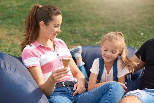 Glückliche mutter und tochter, die spaß haben und draußen spielen, freizeit zusammen in der natur senden, eis essen