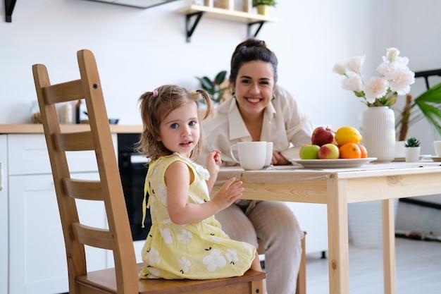 Glückliche mutter und tochter, die zu hause frühstückt