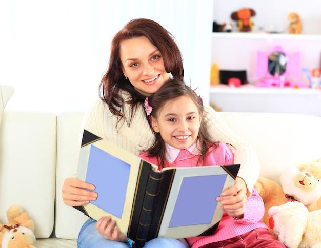 Glückliche mutter und tochter, die zusammen ein buch lesen