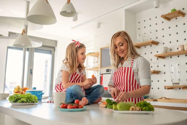 Glückliche mutter und tochter, die zusammen kochen