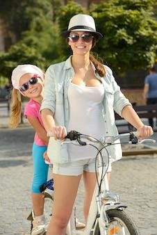 Glückliche mutter und tochter fahren fahrrad.