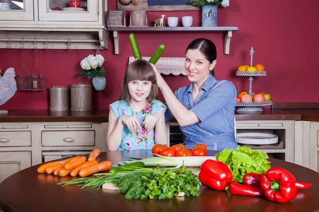 Glückliche mutter und tochter genießen es, gemeinsam in ihrer küche gesunde mahlzeiten zuzubereiten und zu essen. sie machen gemüsesalat und haben zusammen spaß. mama passt auf ihre tochter auf und lernt, wie man kocht.