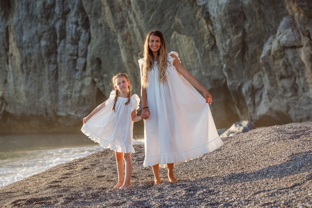 Glückliche mutter und tochter im weißen kleid stehen und halten ihre kleider an der küste während des sonnenuntergangs, vorderansicht.
