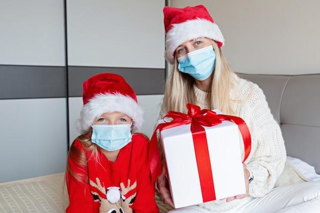 Glückliche mutter und tochter in der medizinischen maske, die geschenkbox hält. weihnachten online-feiertagsfeier