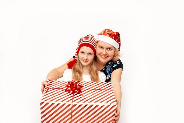 Glückliche mutter und tochter in roten weihnachtsmützen, die ein großes weihnachtsgeschenk in einer schachtel mit einem band und einer schleife halten, die sie geben.