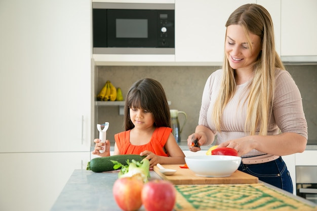 Glückliche mutter und tochter kochen abendessen zusammen. mädchen und ihre mutter schälen und schneiden gemüse für salat auf küchentheke. familienkochkonzept