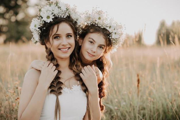 Glückliche mutter und tochter lächeln und umarmen auf dem gebiet im sommer in den weißen kleidern mit borten und blumenkränzen