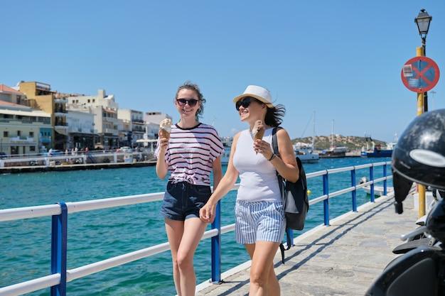 Glückliche mutter und tochter mit eis am sonnigen tag nahe der seepromenade