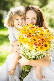 Glückliche mutter und tochter mit großem frühlingsblumenstrauß, die spaß im freien haben
