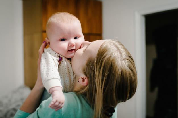 Glückliche mutter und tochter. mutter hält an den händen und küsst kleines baby, konzept glückliche familie, lebensstil. neugeborene. fotoshooting 4-5 monate.