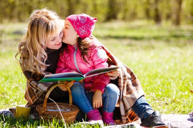 Glückliche mutter und tochter. picknick im grünen park
