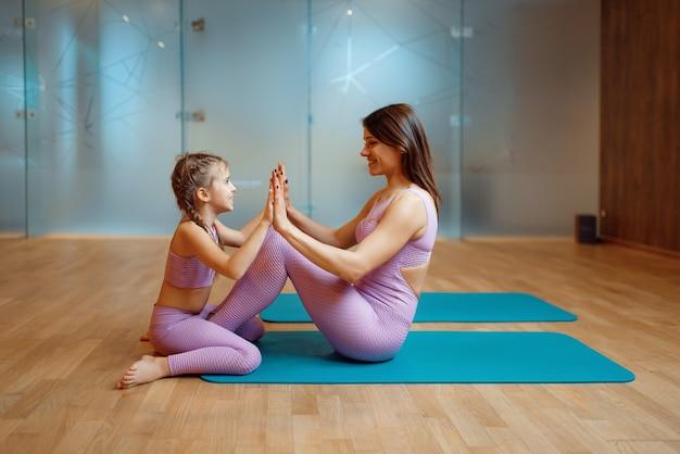Glückliche mutter und tochter posiert auf matten im fitnessstudio, yoga-training. mutter und kleines mädchen in sportbekleidung, frau mit kind beim gemeinsamen training im sportverein