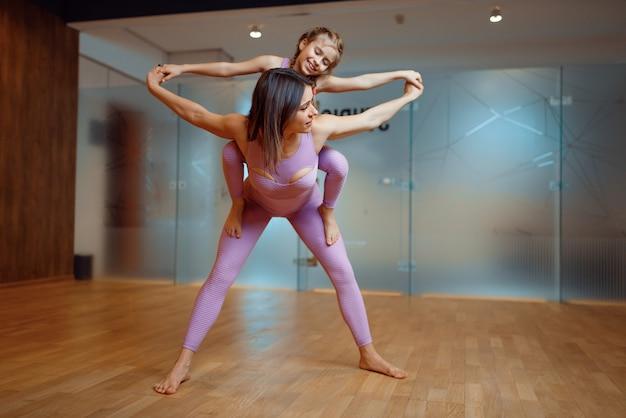Glückliche mutter und tochter posiert im fitnessstudio, yoga-training. mutter und kleines mädchen in sportbekleidung, frau mit kind beim gemeinsamen training im sportverein